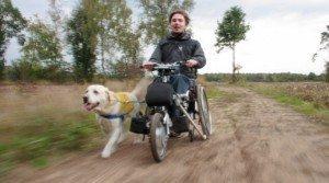 Junger Mann im Rollstuhl fährt mit hellem Labrador Assistenzhund an seiner Seite einen Feldweg hinunter. Bild CC flickr.com:photos:jenrossey.