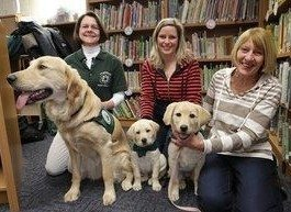 Three smiling ladies kneeling on the floor with three assistance dogs in a library. Photo source: pressofatlanticcity.com
