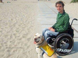 Mann im Rollstuhl genießt seinen Strandurlaub mit seinem Assistenzhund.