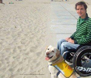 Mann im Rollstuhl genießt seine Ferien mit Assistenzhund am Strand.