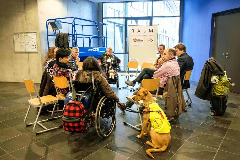 :: Eine Gruppe von acht Erwachsenen sitzt in einem Raum kreisförmig zusammen, scheinbar in ein Arbeitsgespräch vertieft. Eine Rollstuhlfahrerin wird von einem Assistenzhund begleitet, der im Vordergrund des Bildes sitzt.