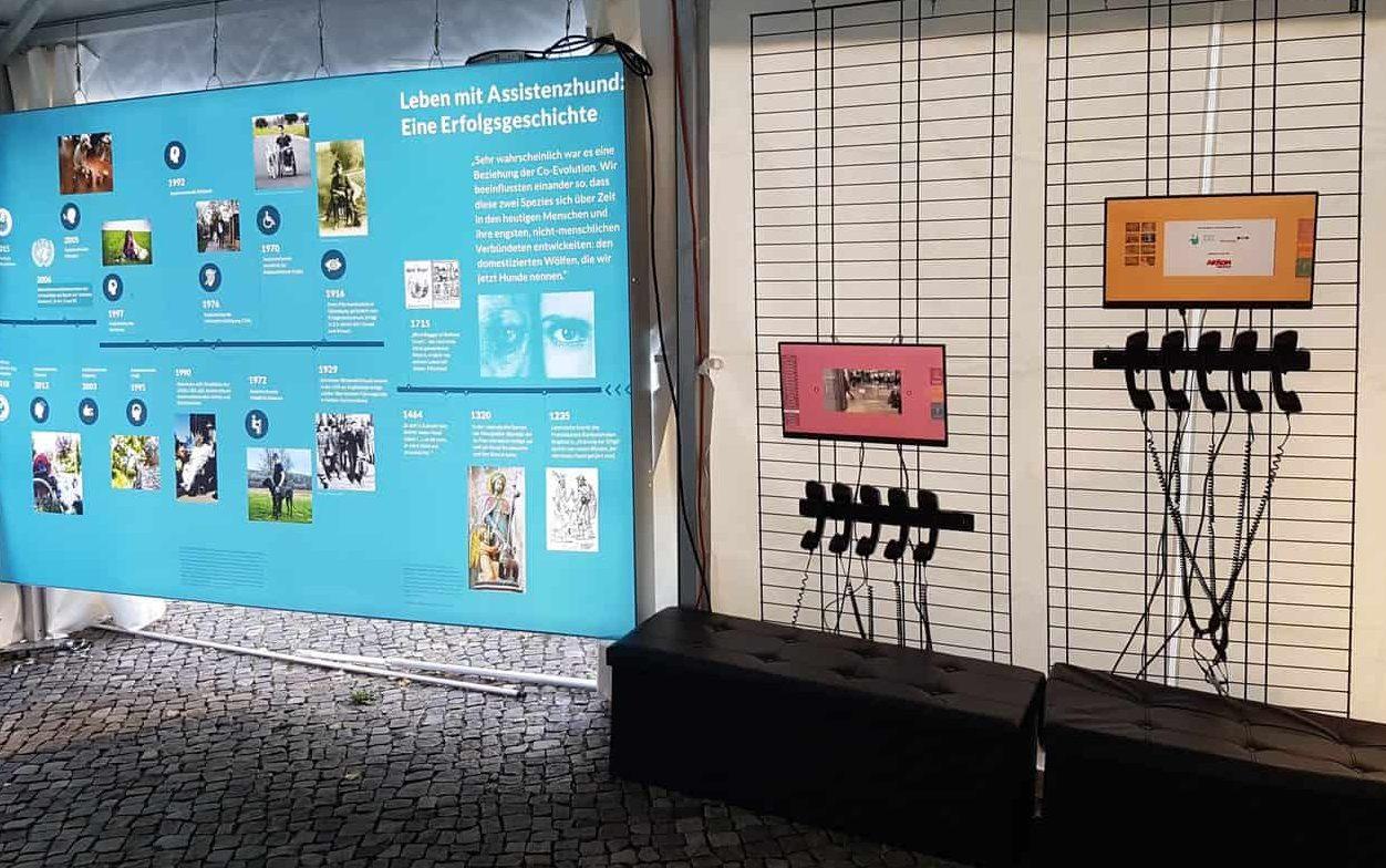 Foto Assistenzhunde Ausstellung :: Auf dem Foto sieht man ein Bild der Assistenzhunde-Ausstellung. Auf einer Fotowand ist die