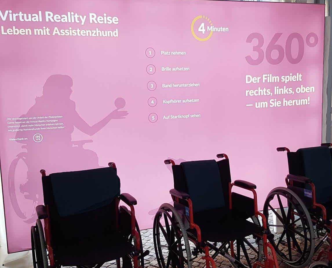 Fotowand Virtual Reality Reise :: Auf dem Foto sieht man die Fotowand Virtual Reality Reise,der Assistenzhunde Ausstellung. Vor der Fotowand stehen drei Rollstühle.
