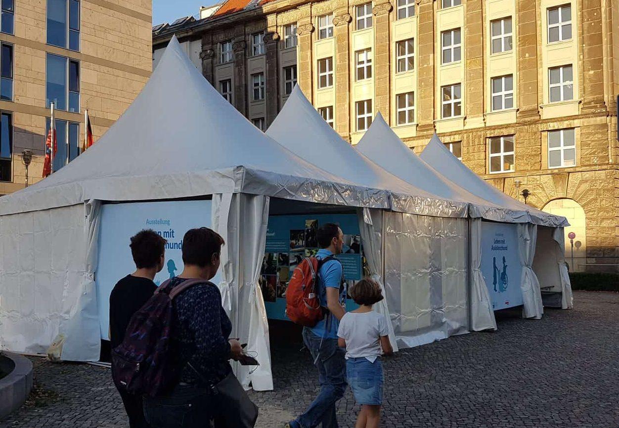Foto der Ausstellungszelte :: Auf dem Foto sieht man vier Menschen vor den Ausstellungszelten der Assistenzhunde-Ausstellung entlang gehen.