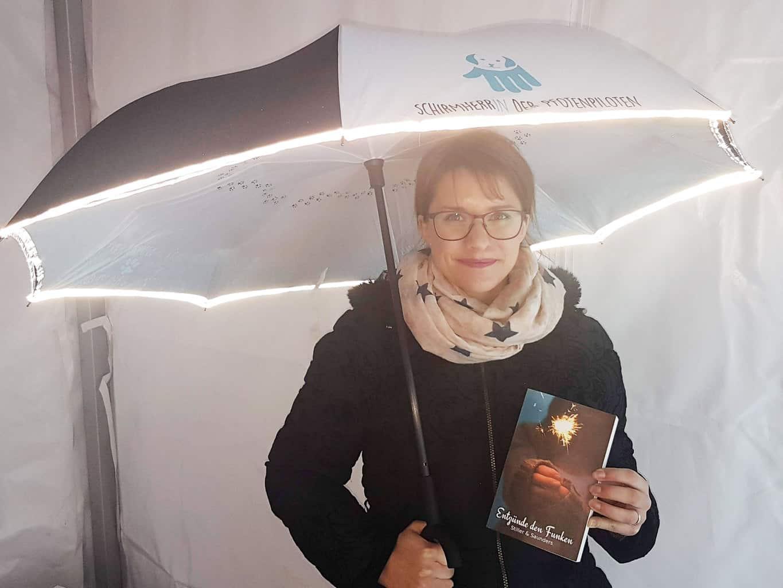 Siiri Saunders, eine der SchirmherrInnen der Pfotenpiloten :: Auf dem Bild sieht man eine junge Frau, mit aufgespanntem Pfotenpilotenschirm. Sie hält das von ihr herausgegebene Buch