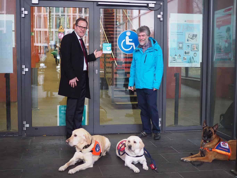 Aufkleberaktion Köln :: Stadtdirektor Dr. Keller und Behindertenbeauftragter Dr. Bell präsentieren den neuen Aufkleber der Zutrittskampagne