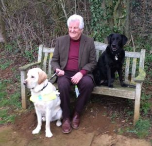 David Adams, EGDF, with old and new guide dog on a bench.