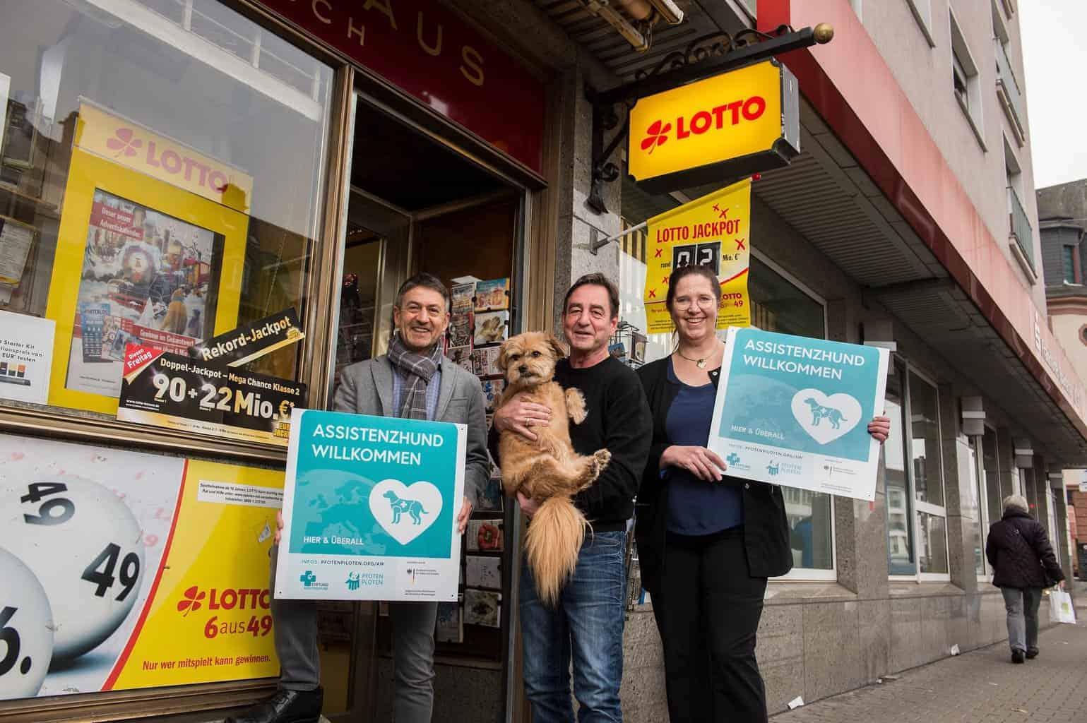 Lotto Hessen Aktion :: Vor der Tür der kleinen Lotto-Verkaufsstelle steht links Herrn Junker von Lotto Hessen mit großem Schild der Zutrittskampagne