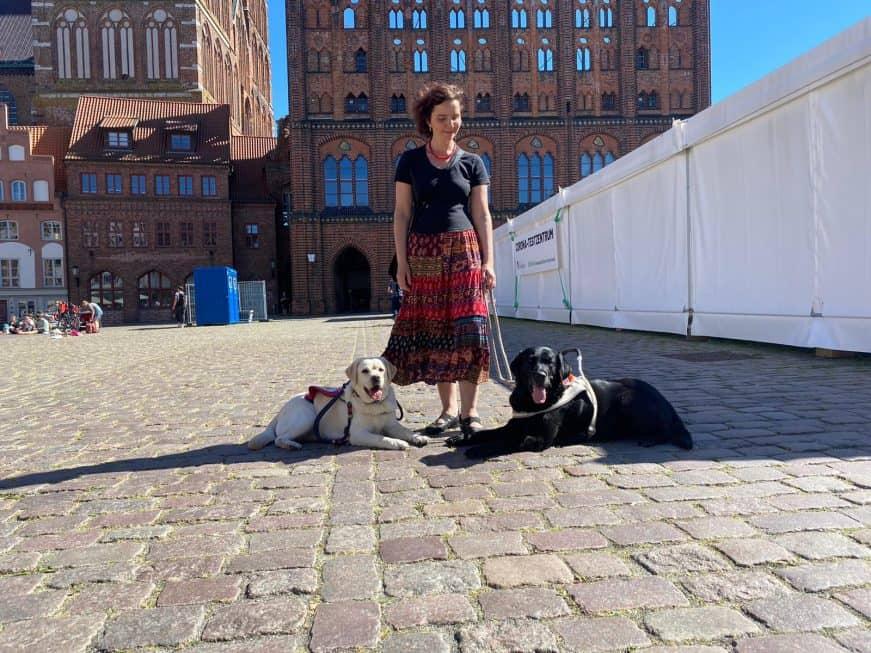 Dr. Reuter auf dem Rathausvorplatz in Stralsund mit Assistenzhunden.