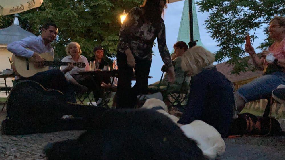 Es ist fast dunkel, Peter Levay spielt Gitarre, es sitzen Menschen bei den Hunden auf dem Boden, andere am Tisch und auf einer nahen Bank.