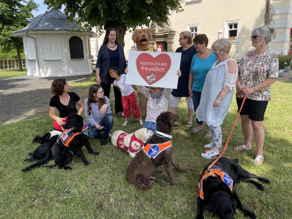 """Die TeilnehmerInnen posieren mit ihren Assistenzhunden für ein Gruppenfoto mit Maskottchen Benji und einem Schild """"assistenzhundfreundlich""""."""