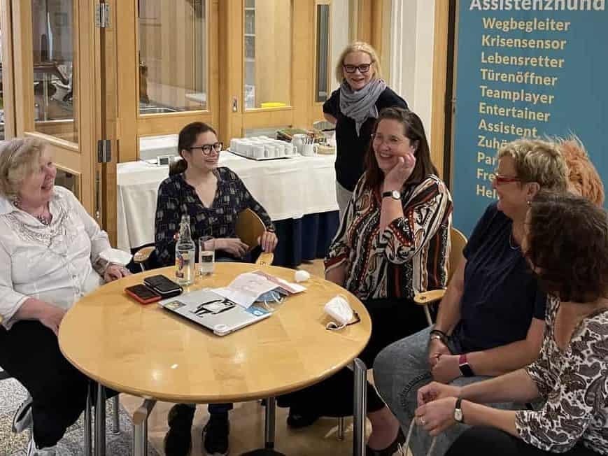 Eine Gruppe Assistenzhundhalterinnen sitzt mit R. Warda an einem runden Tisch im Seminarraum berät sich und hat offensichtlich Spaß.