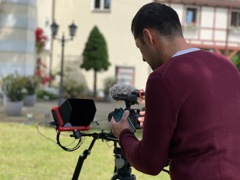 Peter Levay steht hinter der Kamera. Man sieht nur seinen Rücken und wie er etwas an der Kamera einstellt.
