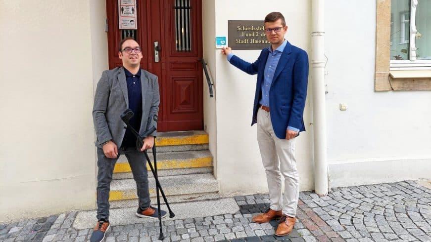 """Ilmenaus Inklusionsbeauftragter Philipp Schiele und Oberbürgermeister Daniel Schultheiß (von links) setzen sich für die Kampagne """"Assistenzhund Willkommen"""" ein. Schultheiß präsentiert den Sticker, den an der Aktion teilnehmende Händler an die Tür kleben, um zu zeigen, dass Assistenzhunde mit ins Gebäude dürfen. Zudem liegt bei diesen Händlern Informationsmaterial aus."""